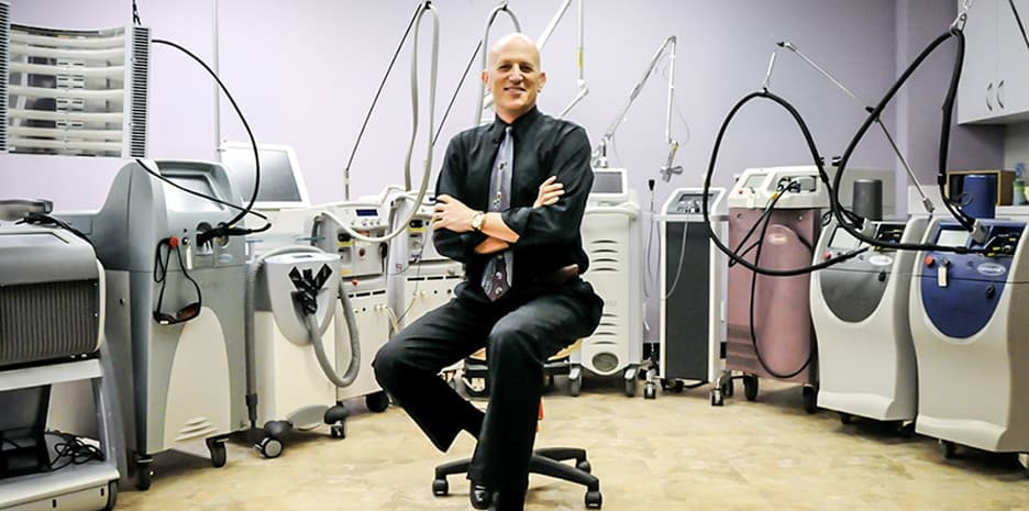 Dr. Asher Milgrom, CEO and Chief Scientist of AMA, with a few of the many lasers used to treat patients at AMA